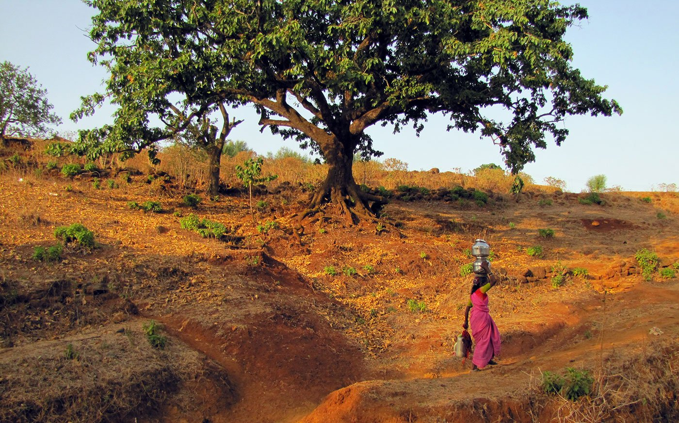 Woman walking up a slope carrying pots on her head