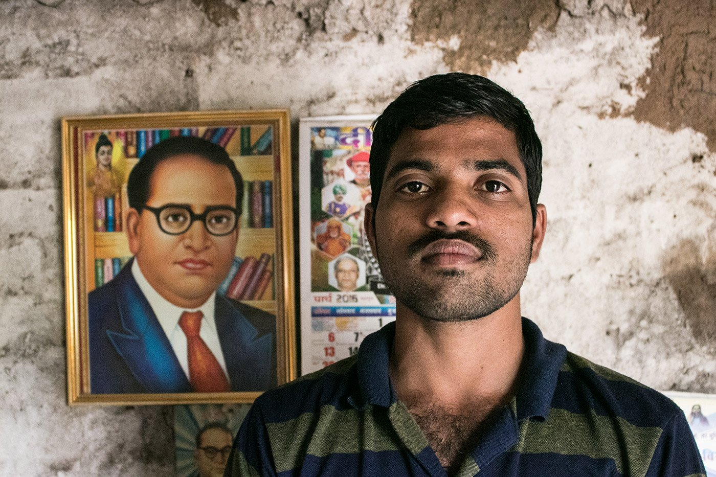 A young man standing in front of a framed illustration of Dr B. R. Ambedkar