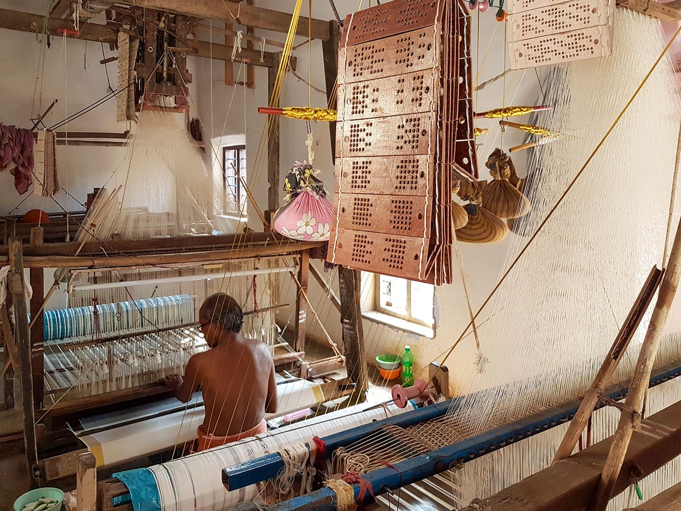 Mani works on a loom inside his home.