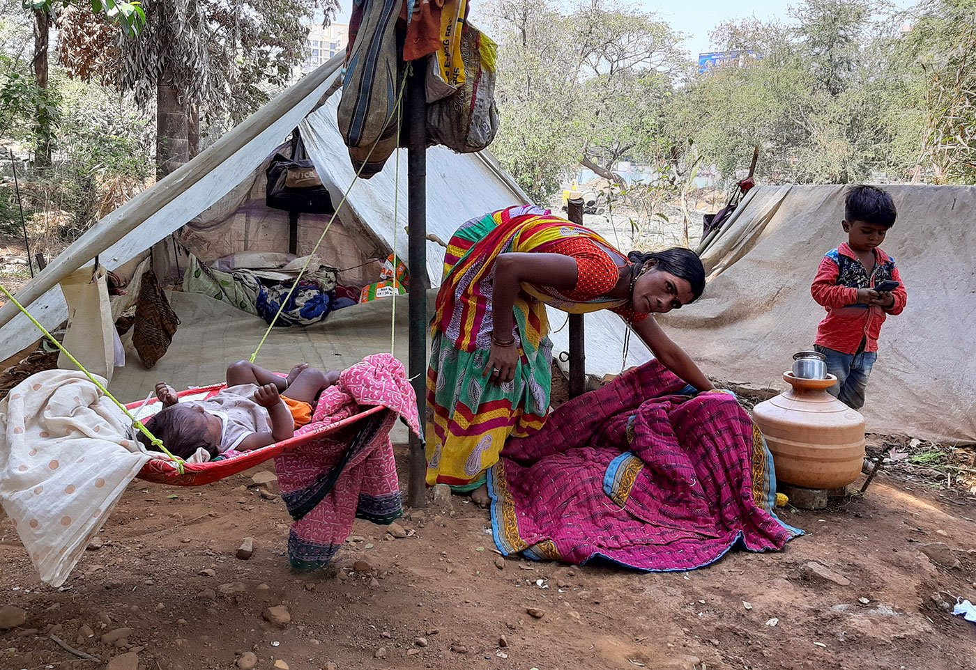 Maya with baby Sheetal and her son Avinash outside their tent