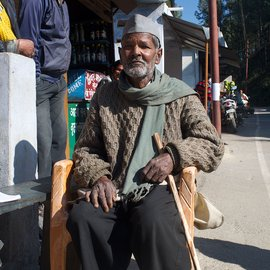 An old man sitting on a chair outside a shop in the mountains