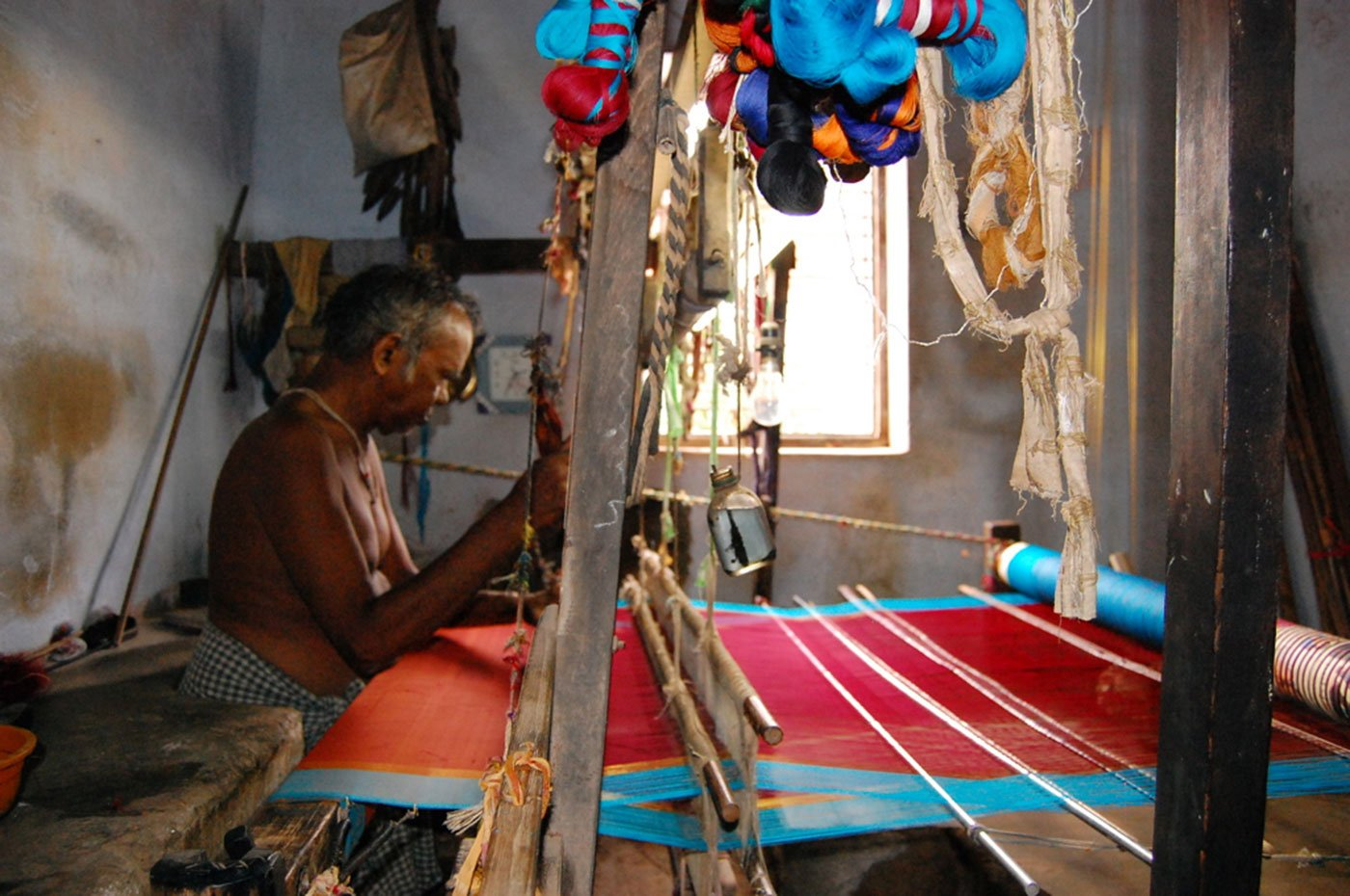 A weaver weaving silk sarees on a handloom