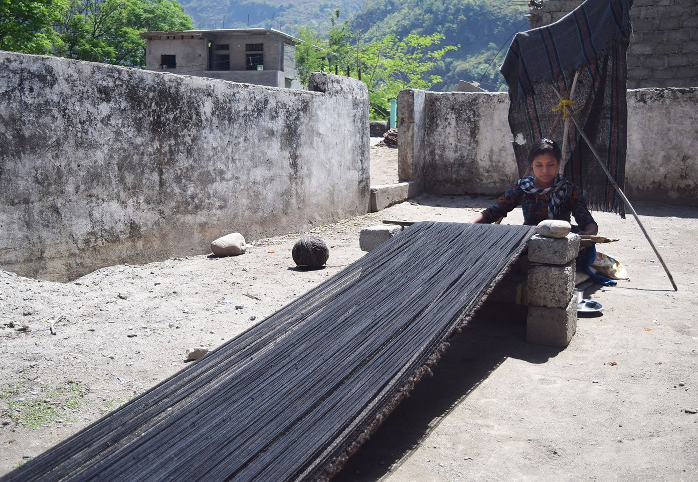 Woman weaving carpet outside her home