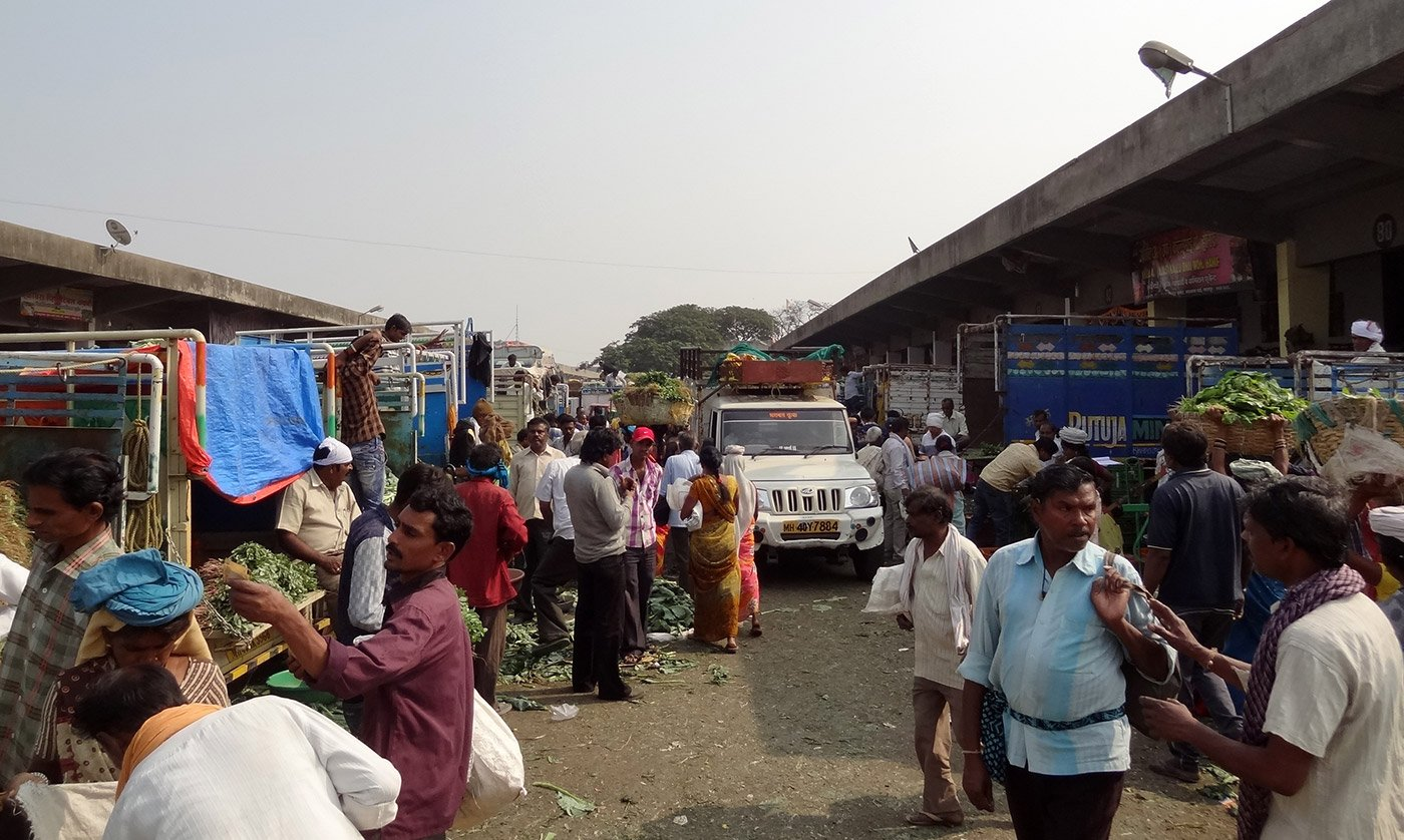 Vegetable market with crowds of people and automobile