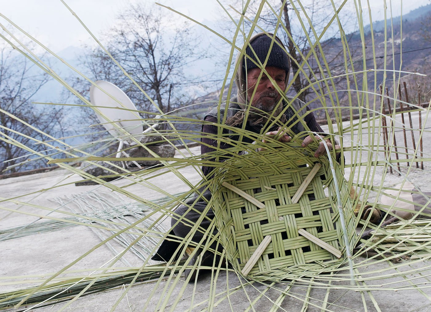 A man sitting on a terrace of a house and weaving bamboo strips into a cylindrical shape