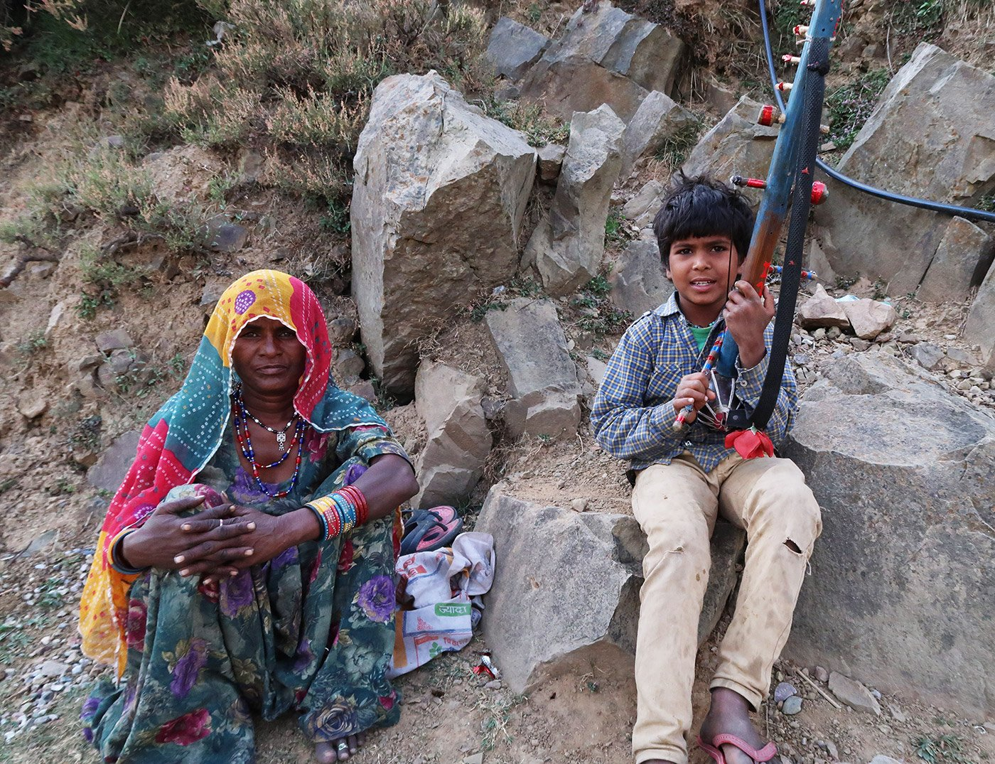 A woman and a young boy sitting amongst rocks. The boy has an instrument called ravanahatha in his hands