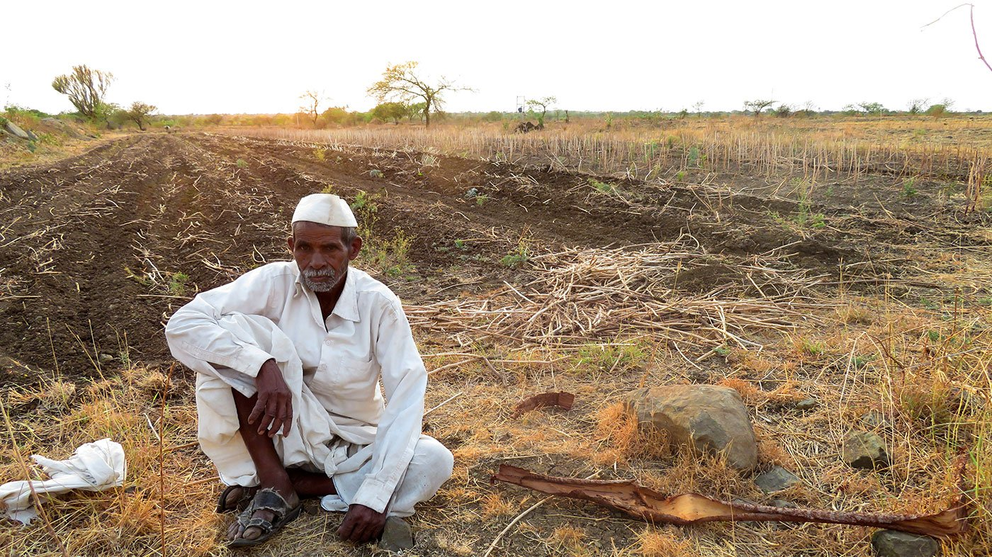 farmer sitting beside his land