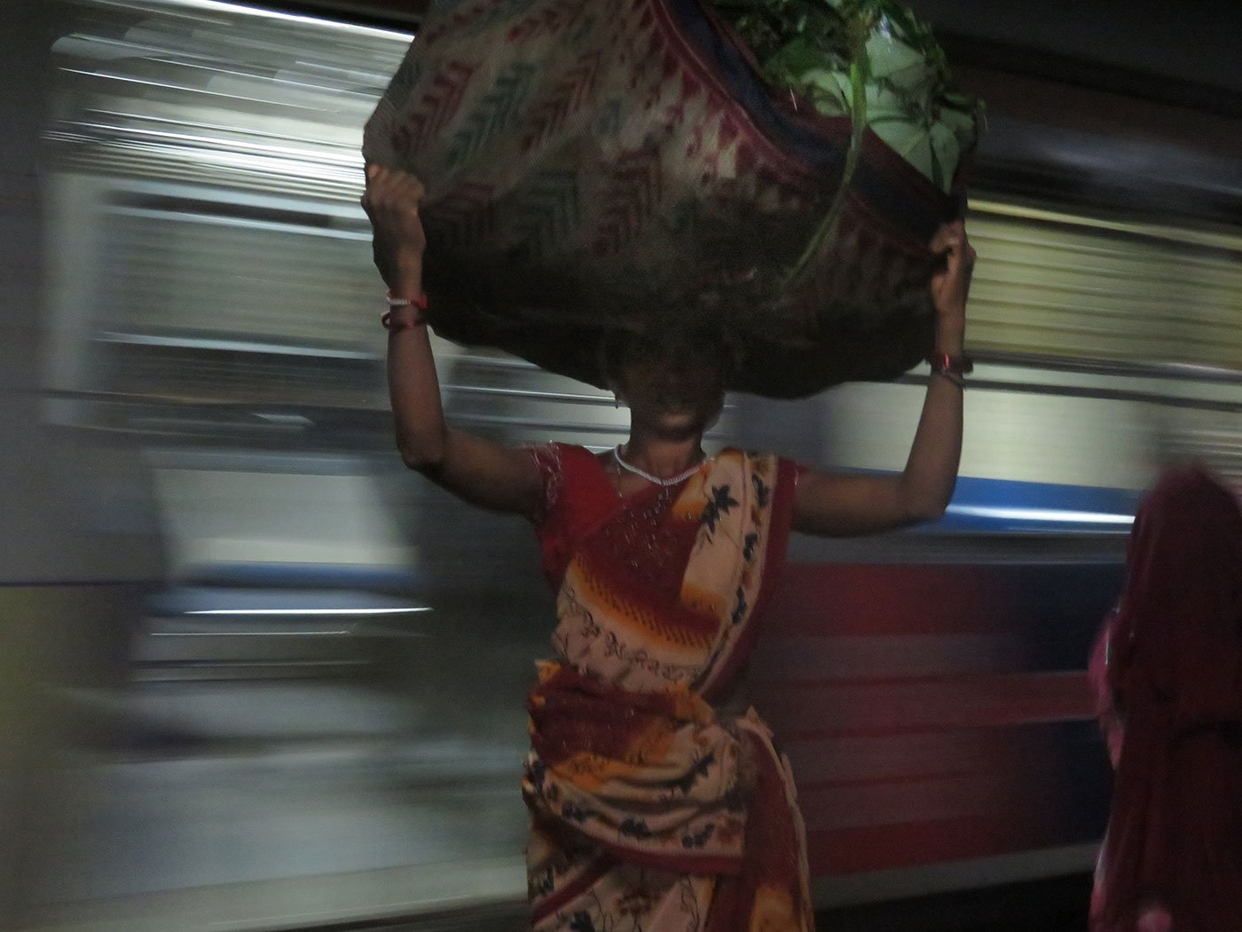 Tulshi, carrying a 35 kg load of palash leaves wrapped in an old sari, at the train station