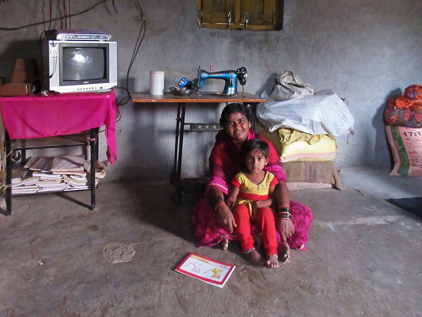 A woman sitting on the floor of her home with a young girl in her lap
