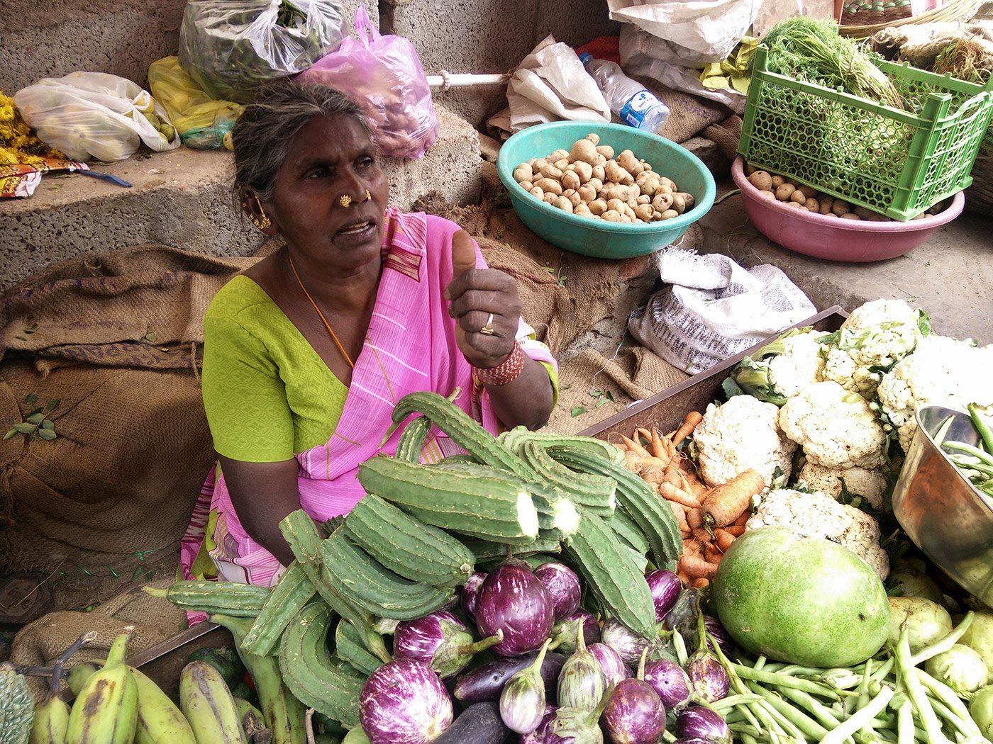 An elderly woman selling vegetables