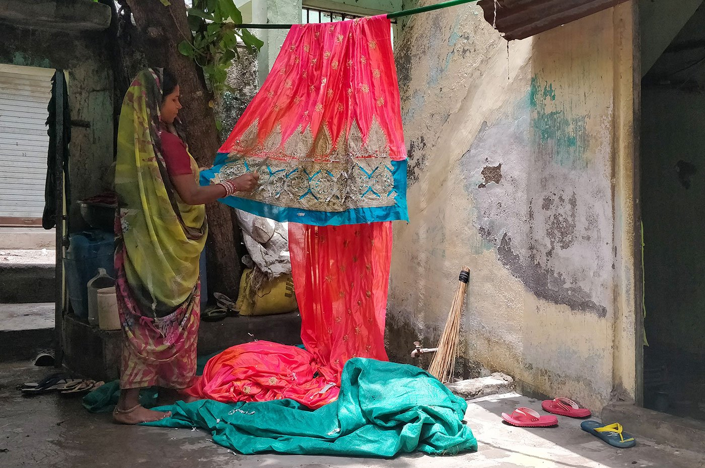 Renuka Pradhan's one-room home in the Mina Nagar area of north Surat turns into her working space every morning. She cuts threads out of more than 75 saris every day. The constant work has led to cuts and bruises on her fingers