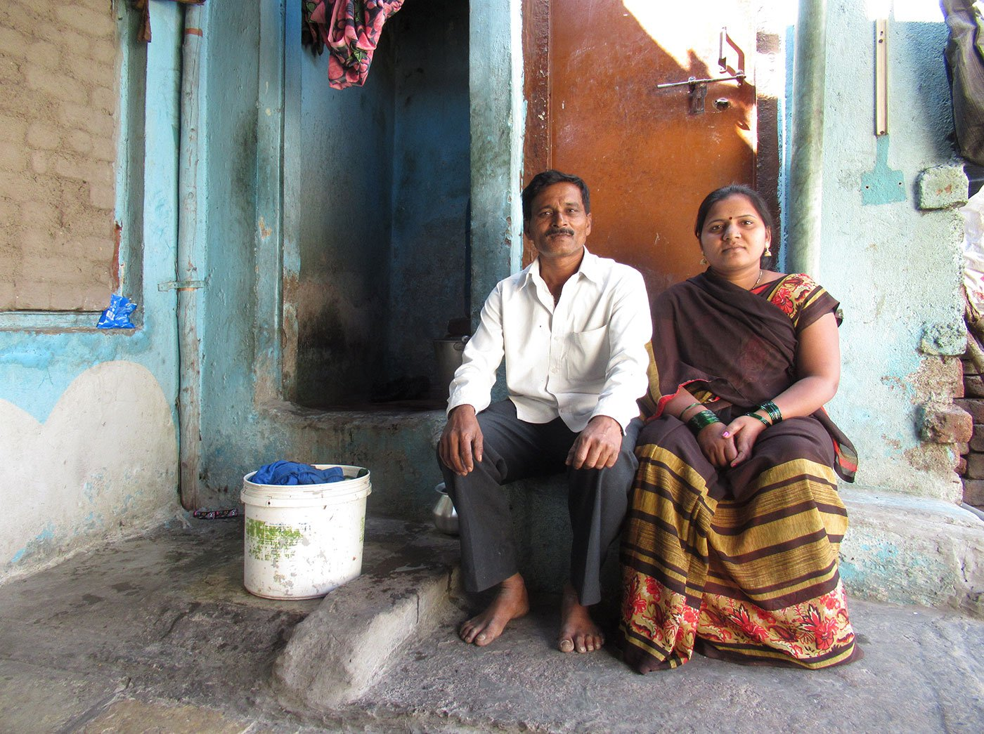 Sarika and Dayanand Satpute sitting outside a house