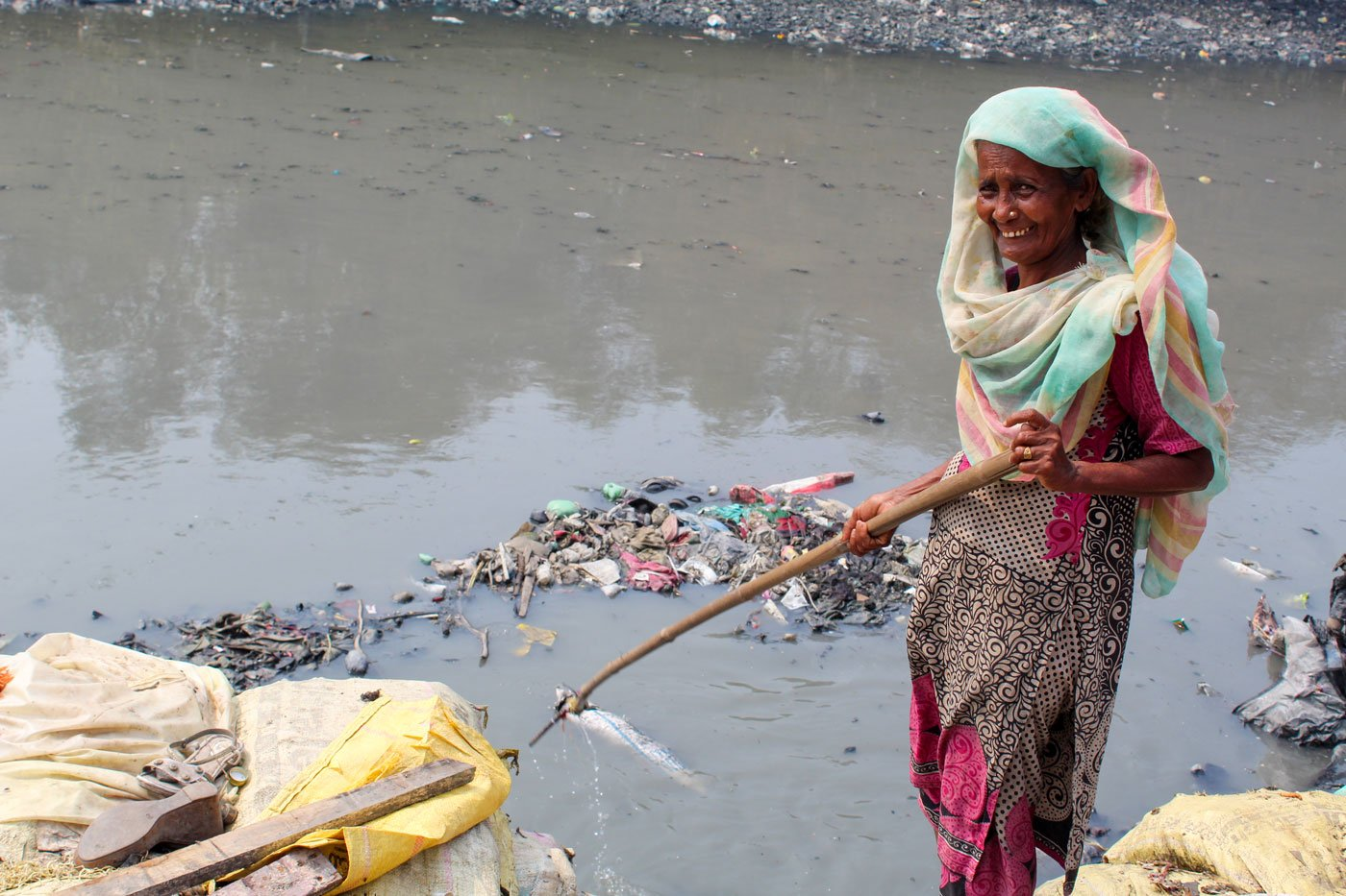 Kitabun Nisa Shaikh fishing out pieces of plastic from the nallah with her stick