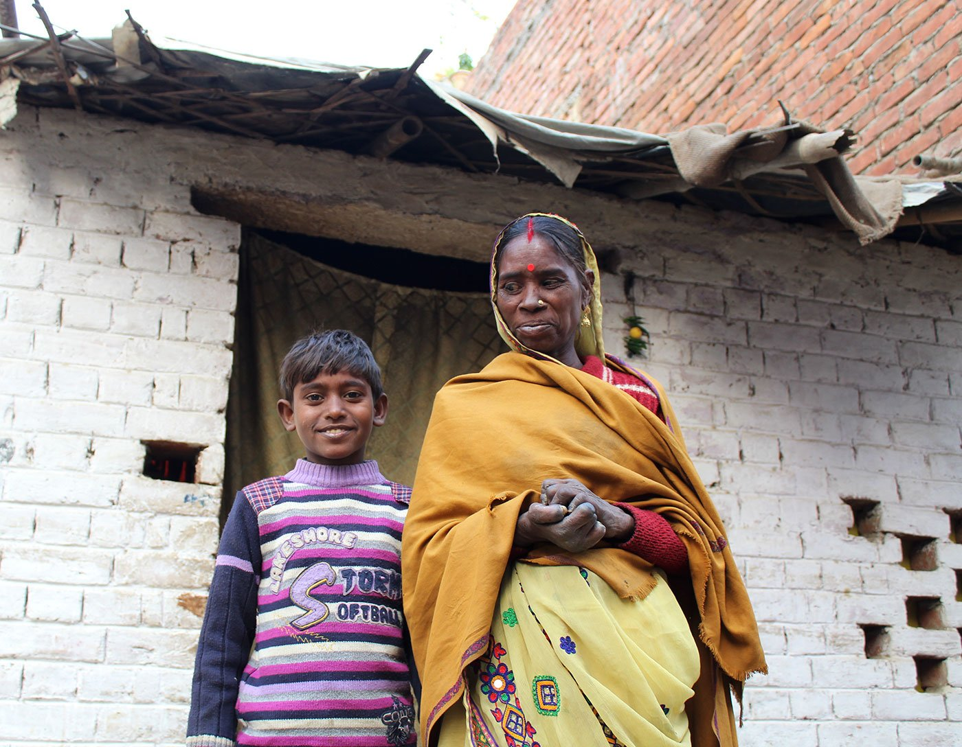 A woman and her son stand outside their house