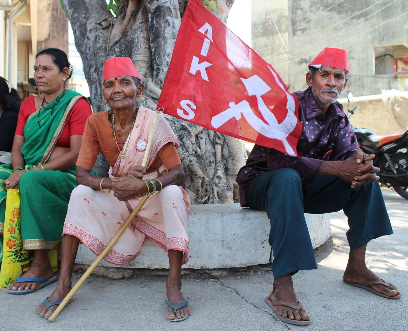 Two women and a man sitting under a tree. One of the women is holding the All India Kisan Sabha flag.
