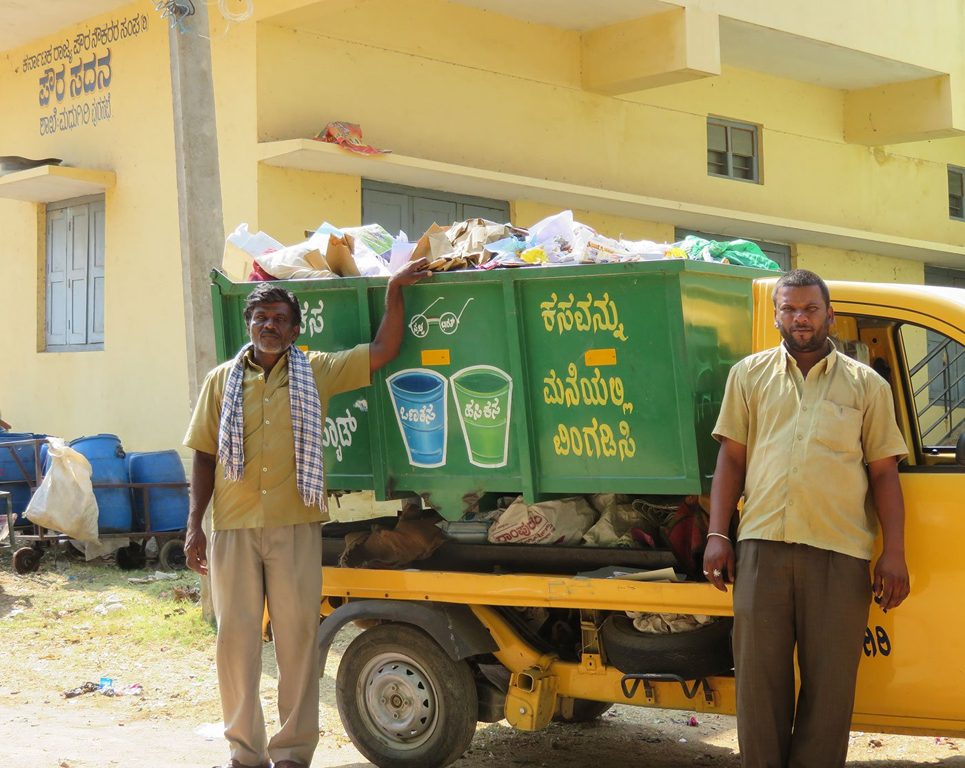 Puttanna (left) and Manjunath (right) standing next to their waste disposal pickup truck. The two men also drive a jetting machine to clean open drains and septic tanks. Often, they must immerse themselves in  these pits to stir the waste and make it more soluble for the technological incompetent machine to do the job