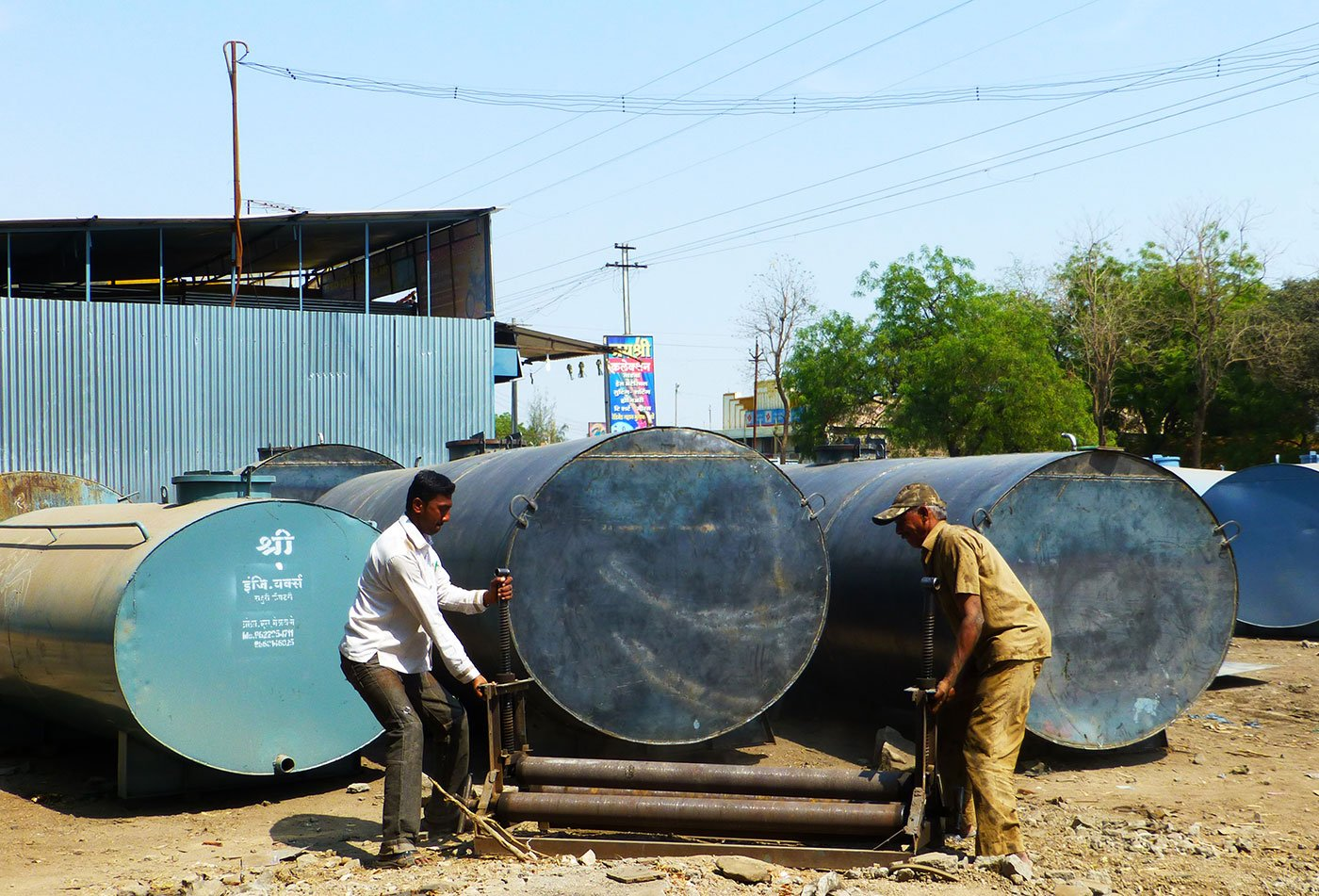 Two men trying to roll a water tank