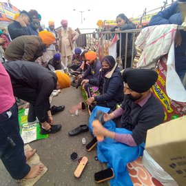 Unmindful of the dust, dirt and occasional rain, Jaswinder Singh Saini and Prakash Kaur, a couple from Delhi, perform sewa at Singhu – cleaning the dirty, muddied shoes of the farmers