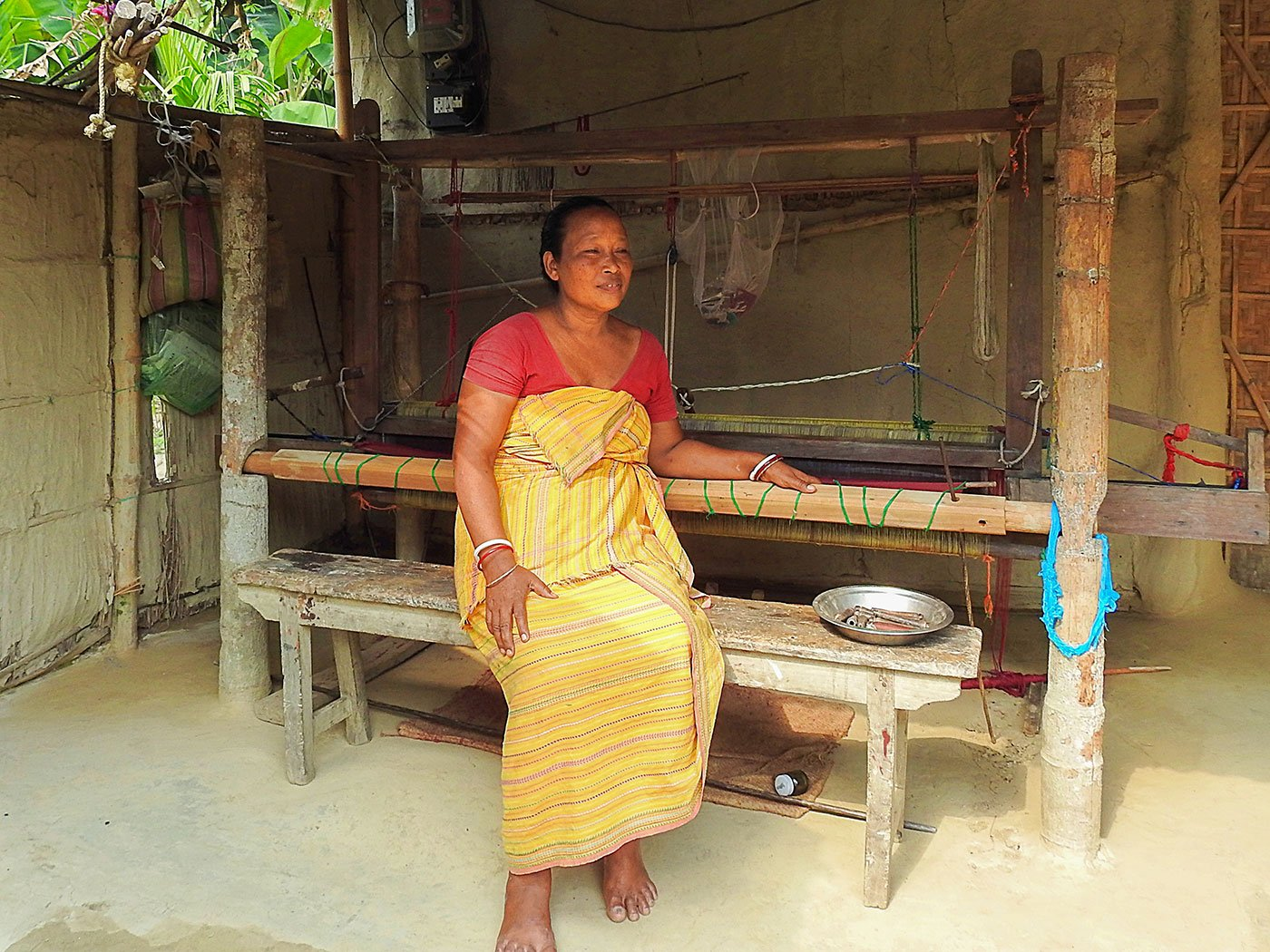 Sama seated at her bamboo pedal loom,
