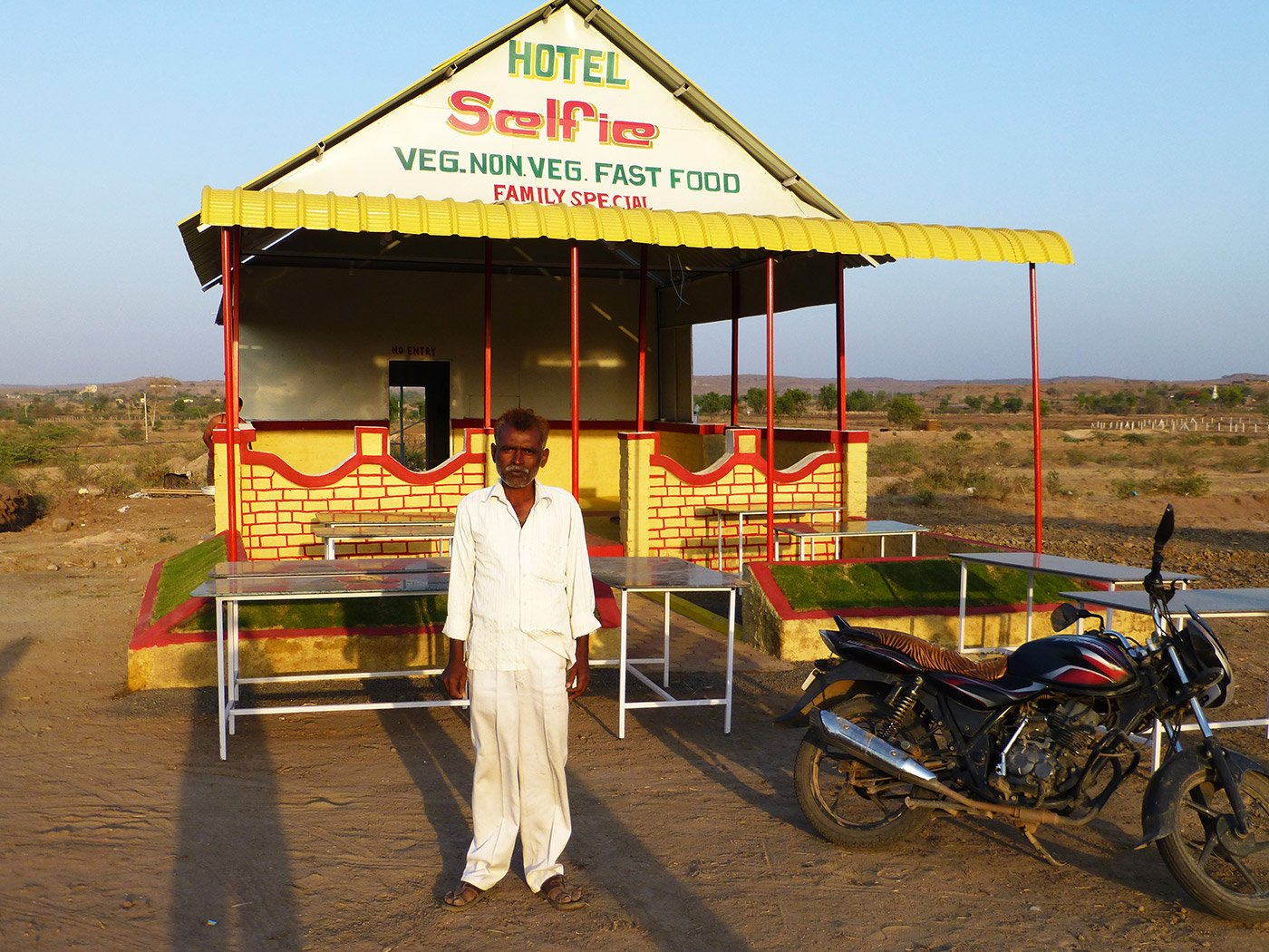 Rafiq Sheikh standing in front of his roadside hotel
