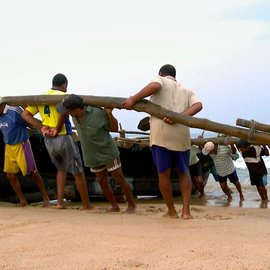 Fishermen pulling a fishing boat onto the beach