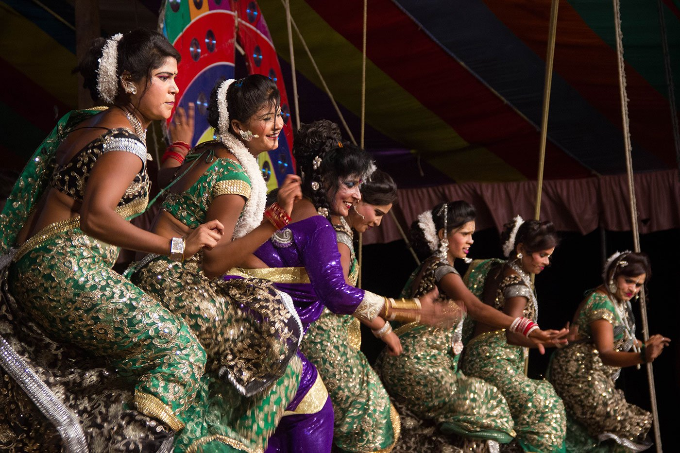 Women in saris dancing on a stage at a tamasha performance