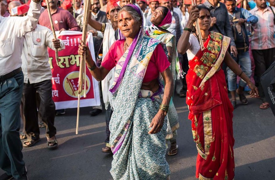 A woman marching alongside other people, holding a flag