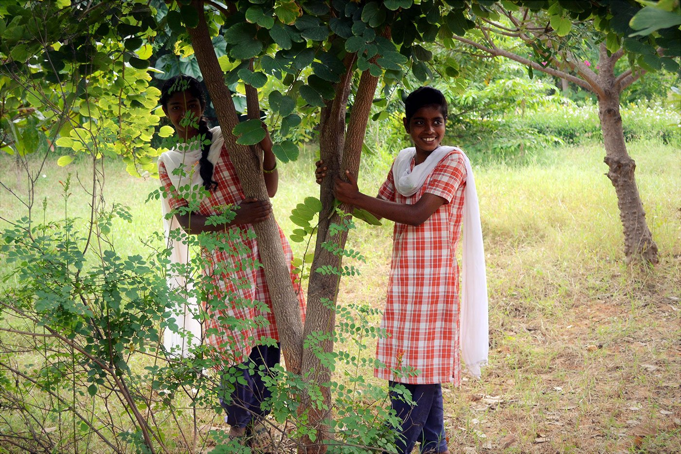 Two girls standing under a tree