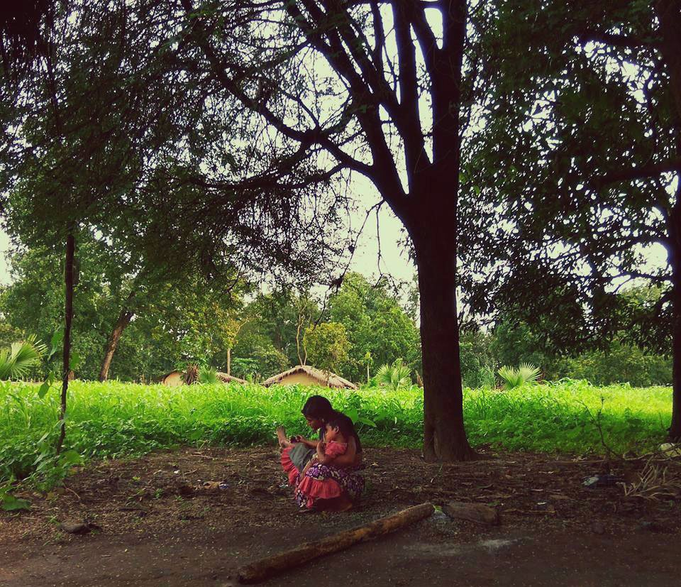 A woman with her child under a mahua tree in Farsegarh village, Bijapur district; she is a forest dependent farmer who was returning from the weekly market or haat with her child