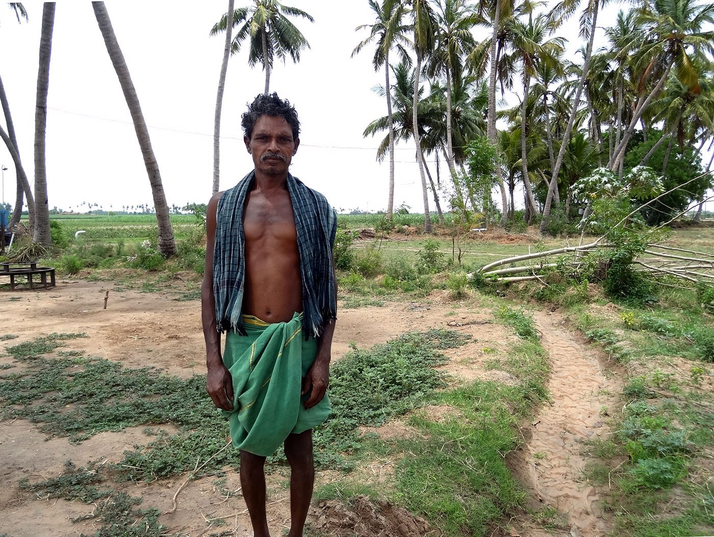 K Lekan, fondly known in his village as Settu, stands against the backdrop of wilting farms in his village Thayanur, 25 km from Trichy town, lucky to have survived a suicide bid earlier this year amidst a raging drought.