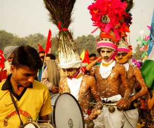 Dancers from Nandurbar district in Maharashtra in traditional Bhil and Pawra Adivasi attire, drums and chiming bells.