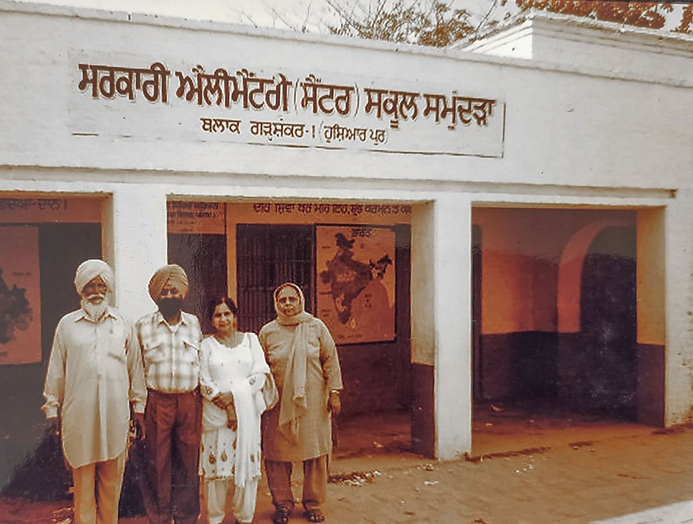Bhagat Singh Jhuggian and his wife Gurdev Kaur, with two friends in between them, stand in front of the school, since renovated, that threw him out in 1939