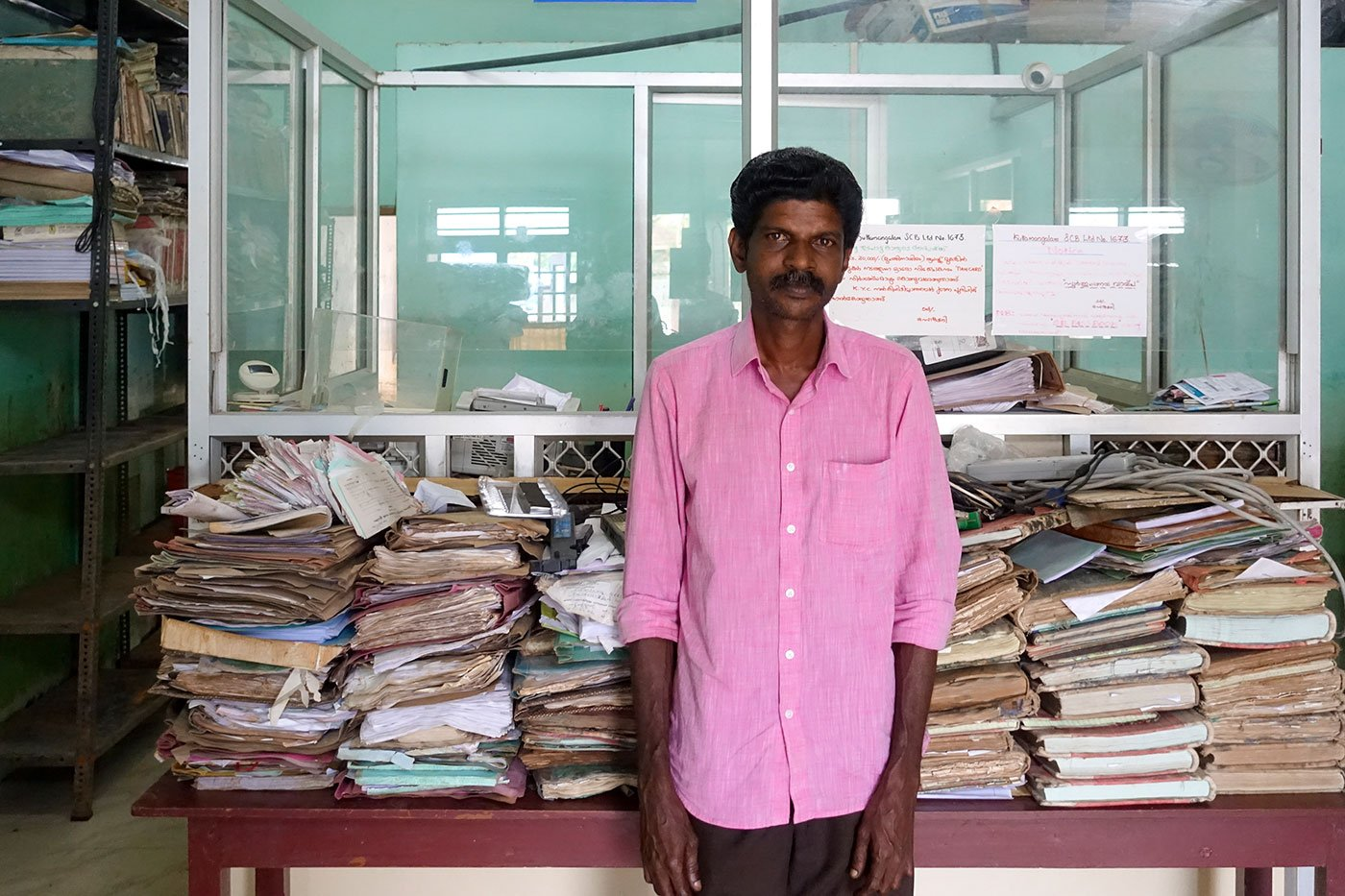 Girish Kumar H, the cashier, standing next to records full of fungus and mould