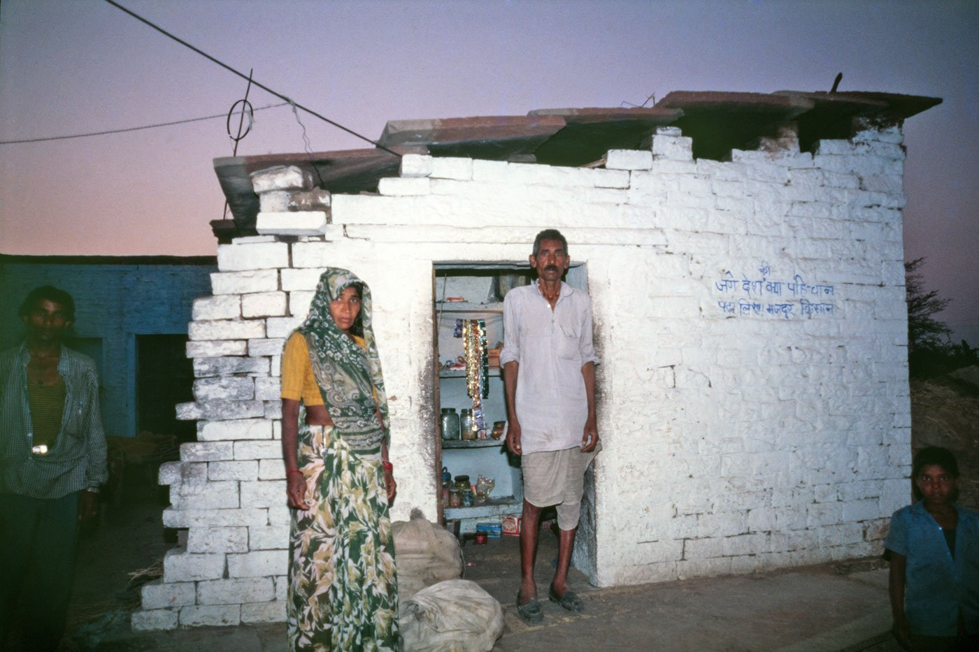 Mangi Lai Jatav and his wife in Naksoda village in Dholupur district. A man and a woman standing outside a hut