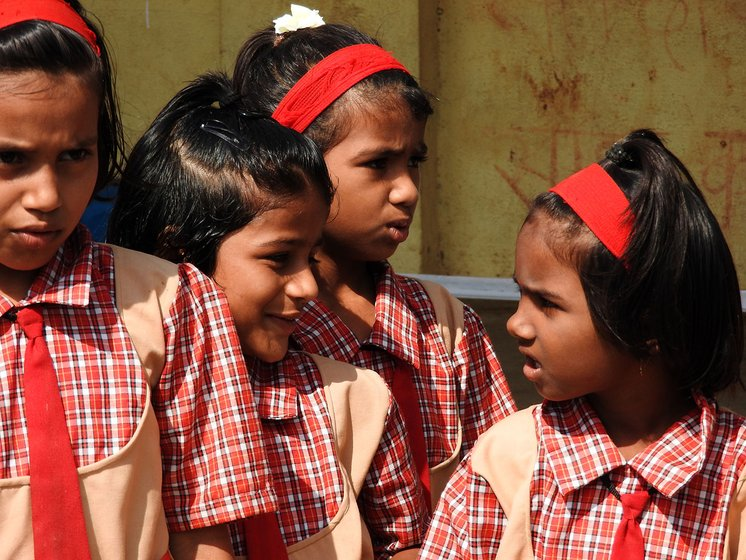 Girls singing outside a school