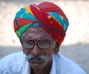 A man with a colourful head gear