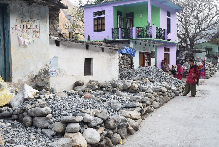 Woman on road outside house. Road lined with stacked stones