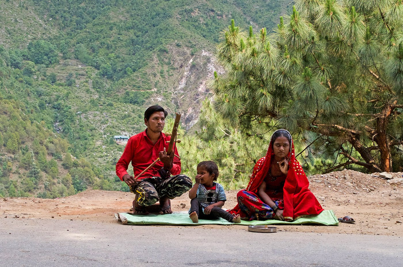 A man and his wife sitting on the side of the road in the moutains. the man is holding an instrument called ravanahatha in his hands