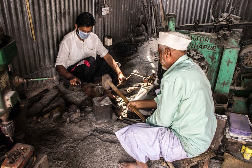 Dilawar Shikalgar – here with and his son Salim – uses a hammer to shape an iron block into a nut cutter or adkitta of distinctive design and durability