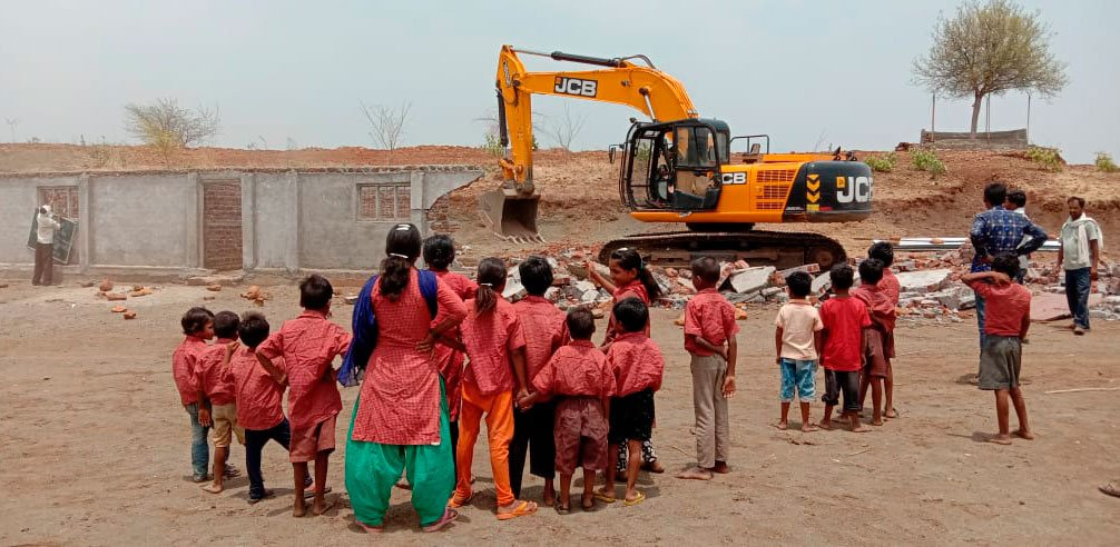 Schoolchildren looking at the bulldozer demolish their school