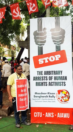 M.S. Shantkumar shuffles to the side to make way for a poster protesting the clamp down on civil liberties