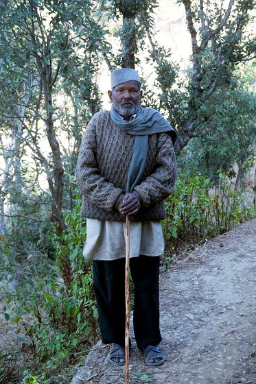 An old man with a stick standing on a mountain path