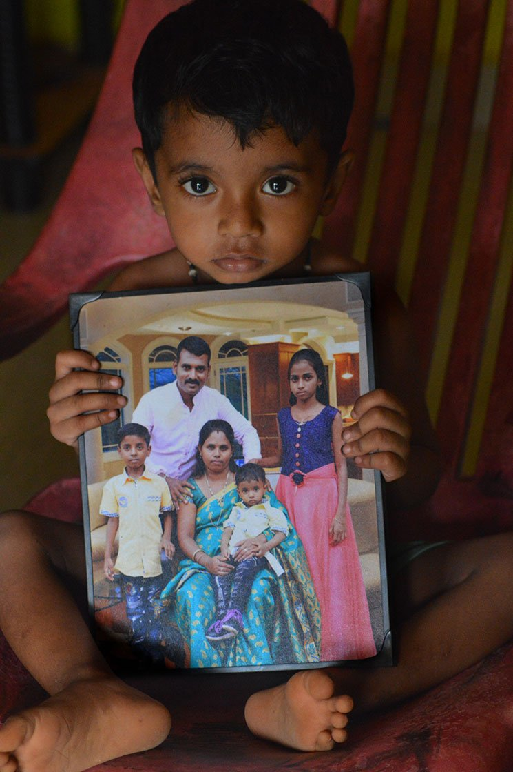A young boy sitting on a chair and holding a framed photograph of his family