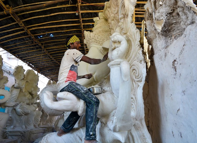 Babban sitting on the hand of a ganesh idol and painting it