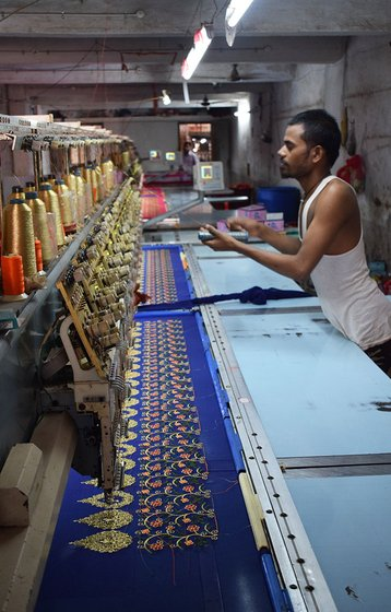 A young worker works on an embroidery machine in a unit in Fulwadi