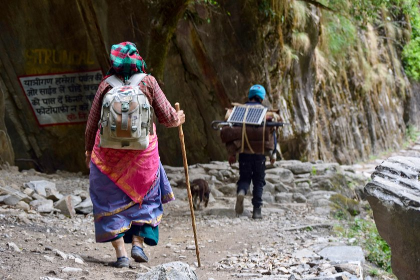 Sukhmati Devi is trudging along the 70 km route to her village Kuti in Vyas valley in Dharchula in Pithoragarh district of Uttarakhand. Before her, a porter is carrying her basic necessities including grains, packet of biscuits and a solar panel for charging of phone and torches