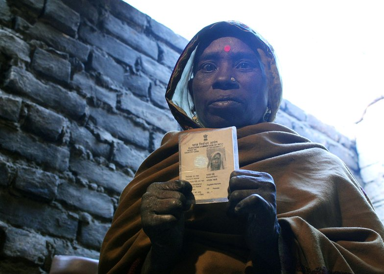 A woman showing her Voter ID card
