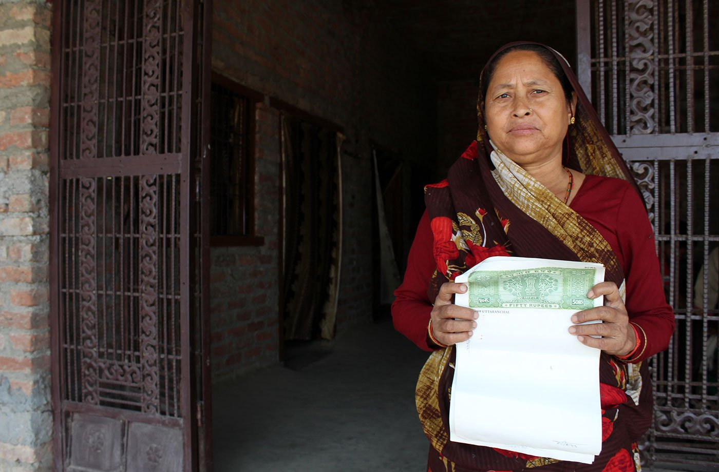 Kamla Devi in front of her home in the village of Pindari (Udham Singh Nagar), Uttarakhand. She holds a blank stamp paper signed by her husband Harish Chandra