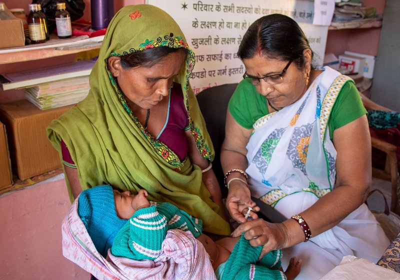 Niranjana Joshi, the ANM at the health sub centre administers the first ever vaccines to Hira Ninama's fifth daughter