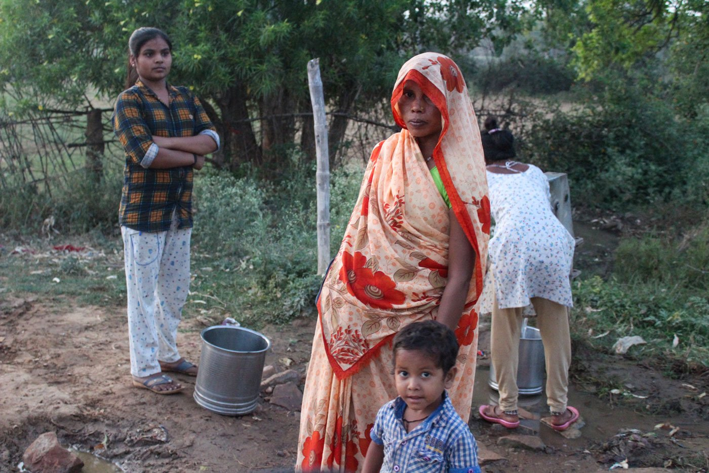 Sushma Devi with her youngest child at the village hand-pump; she ensures that her saree pallu doesn't slip off her head